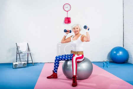 happy sporty senior woman sitting on fitness ball and exercising with dumbbells