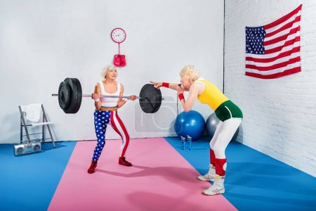sporty senior woman blowing whistle and looking at elderly sportswoman lifting barbell