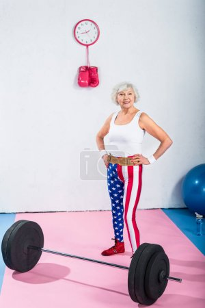patriotic senior sportswoman standing with hands on waist and smiling at camera