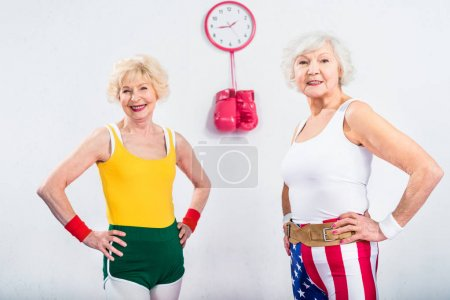 Photo for Happy senior sportswomen standing with hands on waist and smiling at camera - Royalty Free Image
