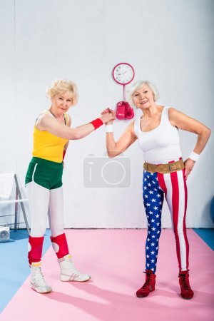 happy senior sportswomen exercising together and smiling at camera in gym