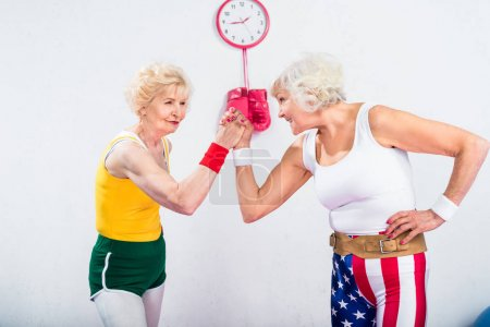 smiling senior sportswomen wrestling and looking at each other in gym