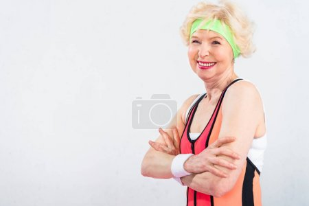portrait of beautiful happy sporty senior woman standing with crossed arms isolated on grey