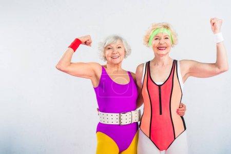 Foto de Deportistas seniors felizes mostrando músculos y sonriendo a cámara aislada en gris - Imagen libre de derechos