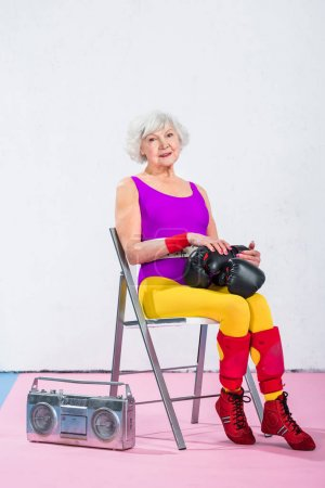 beautiful sportive senior woman with boxing gloves sitting and smiling at camera