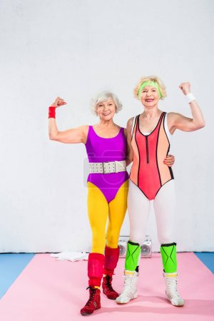 cheerful senior sportswomen showing muscles and smiling at camera