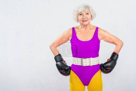 happy senior sportswoman in boxing gloves standing with hands on waist and smiling at camera isolated on grey