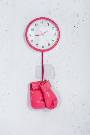 close-up view of pink boxing gloves hanging at wall clock on white
