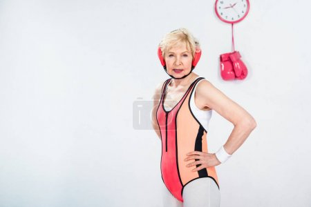 confident senior sportswoman standing with hands on waist and looking at camera