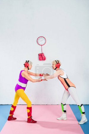 full length view of senior female wrestlers in head protection fighting together