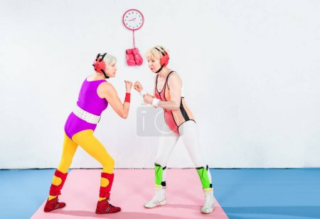 side view of senior female wrestlers in head protection fighting together