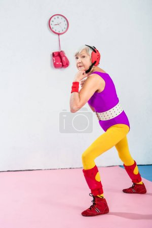 full length view of senior female boxer training and looking at camera