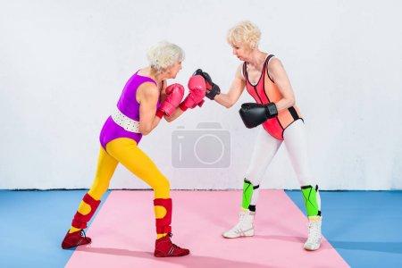 Photo pour Vue latérale des sportives seniors en gants de boxe se battant et se regardant - image libre de droit