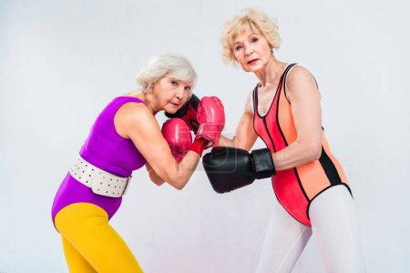 Photo for Side view of senior sportswomen in boxing gloves training and looking at camera isolated on grey - Royalty Free Image