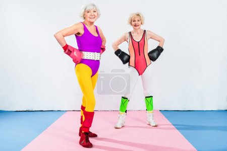 Photo for Full length view of sportive senior ladies in boxing gloves standing with hands on waist and smiling at camera - Royalty Free Image
