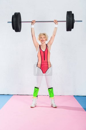 full length view of senior sportswoman holding barbell and smiling at camera