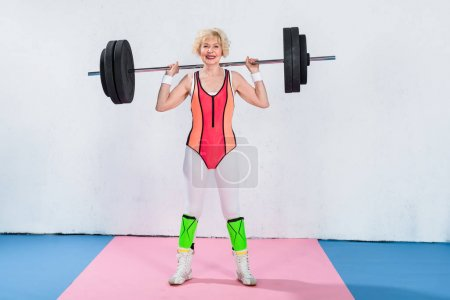 full length view of happy senior sportswoman lifting barbell and smiling at camera