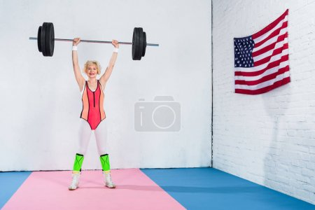 full length view of sporty senior woman lifting barbell and smiling at camera