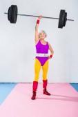 full length view of senior sportswoman lifting barbell and smiling at camera