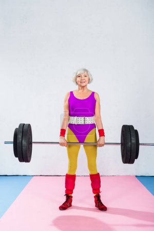 sporty senior lady holding barbell and smiling at camera