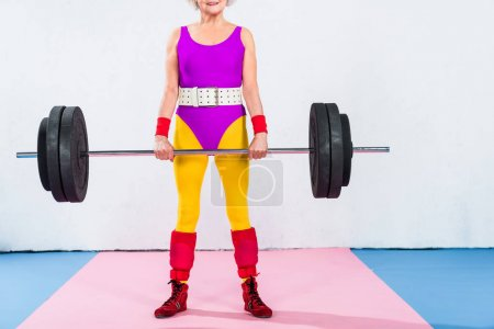 cropped shot of smiling senior woman in sportswear lifting barbell