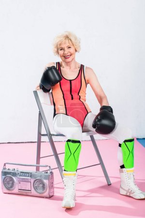 sporty senior woman in boxing gloves sitting with tape recorder and smiling at camera