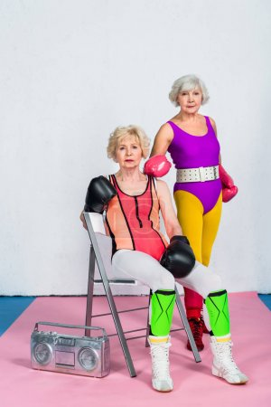sporty senior women in boxing gloves and sportswear looking at camera
