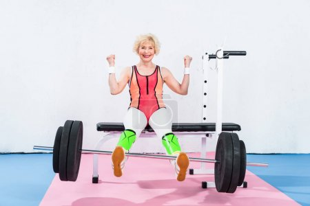 happy senior sportswoman lifting barbell with legs and smiling at camera