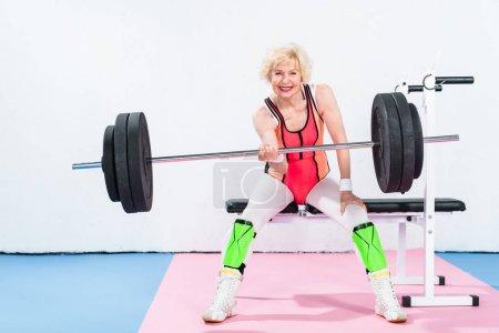 happy senior sportswoman lifting barbell and smiling at camera