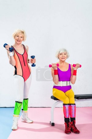 sporty senior women in sportswear exercising with dumbbells and smiling at camera in gym