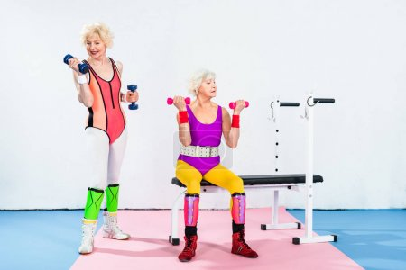 sporty senior women in sportswear exercising with dumbbells in gym