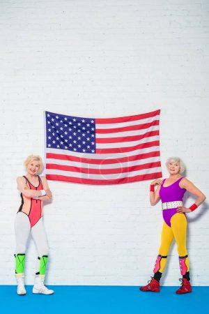 full length view of beautiful senior sportswomen standing near american flag and smiling at camera