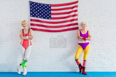 beautiful senior sportswomen standing with crossed arms near american flag and smiling at camera