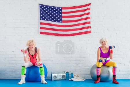 sportive senior women exercising with dumbbells and smiling at camera while sitting on fitness balls in gym
