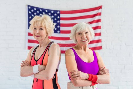 beautiful sporty senior women standing with crossed arms and smiling at camera against american flag