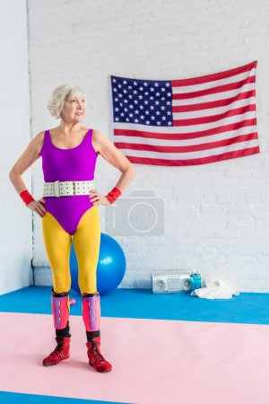 confident senior sportswoman standing with hands on waist and looking away in gym