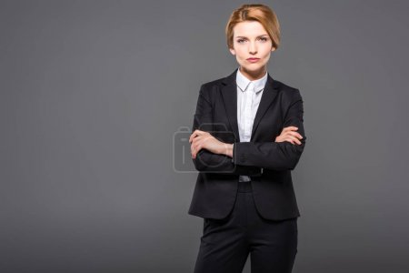 serious businesswoman posing in suit with crossed arms, isolated on grey