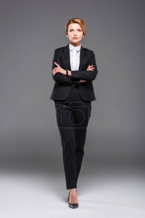 Photo for Confident businesswoman posing in formal wear with crossed arms, isolated on grey - Royalty Free Image