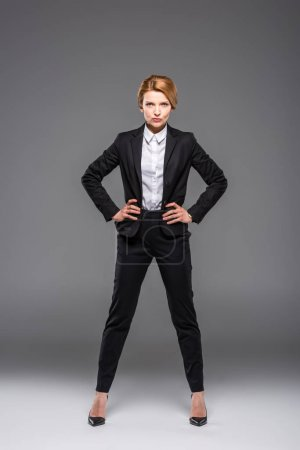 confident businesswoman posing in black suit, isolated on grey