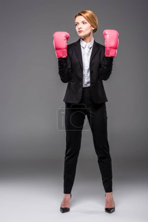Photo for Confident businesswoman posing in suit and pink boxing gloves, isolated on grey - Royalty Free Image