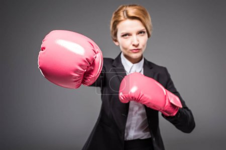 selective focus of businesswoman in suit and pink boxing gloves, isolated on grey