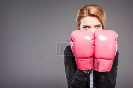 blonde businesswoman in suit and pink boxing gloves, isolated on grey