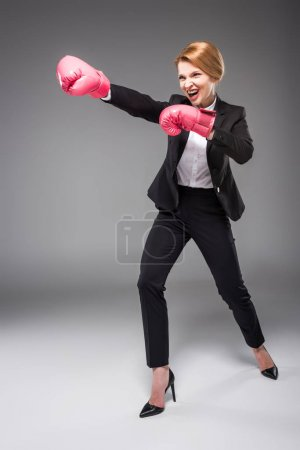 excited businesswoman in suit and pink boxing gloves, isolated on grey