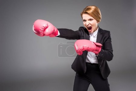 aggressive businesswoman yelling in pink boxing gloves, isolated on grey