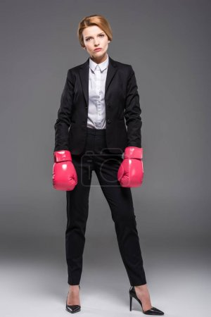 Photo for Serious businesswoman posing in suit and pink boxing gloves, isolated on grey - Royalty Free Image