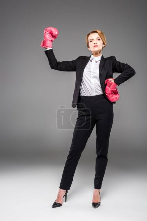 strong businesswoman posing in formal wear and boxing gloves, isolated on grey