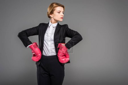 strong businesswoman posing in suit and pink boxing gloves, isolated on grey