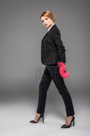 Photo for Serious businesswoman in suit and pink boxing gloves, isolated on grey - Royalty Free Image