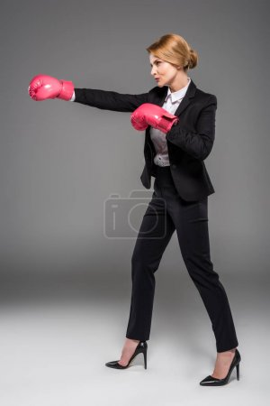 Photo for Executive businesswoman in suit and pink boxing gloves, isolated on grey - Royalty Free Image