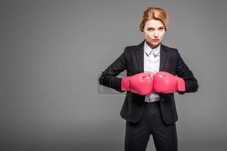 businesswoman in suit and formal wear and pink boxing gloves, isolated on grey